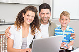 Happy little boy using laptop with parents at table