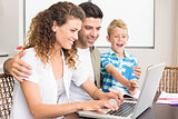 Laughing little boy using laptop with parents at table