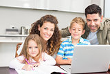 Happy parents colouring and using laptop with their children