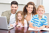 Happy parents colouring and using laptop with their young children