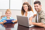 Happy parents sitting with son using tablet and laptop