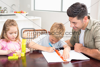 Father helping son with homework with little girl playing with blocks