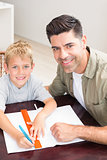 Happy father helping son with homework at table