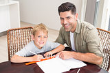 Smiling father helping son with homework at table