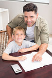 Cheerful father helping son with his math homework at table