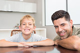 Father and son smiling at camera at the table