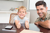 Father and son giving thumb up smiling at camera at the table