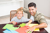 Happy father and son making paper shapes together at the table