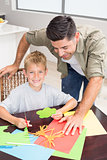 Father and smiling son making paper shapes together at the table