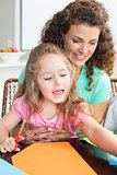 Cheerful little girl doing arts and crafts with mother at the table