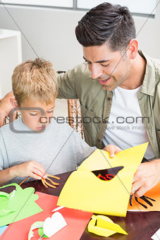 Little boy making paper shapes with father at the table