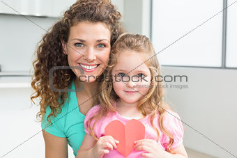 Cute little girl showing paper heart with mother