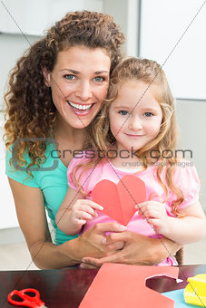 Cute little girl showing paper heart sitting on mothers lap