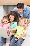 Cheerful family sitting on sofa looking at laptop