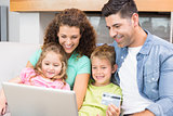 Happy family sitting on sofa using laptop together to shop online