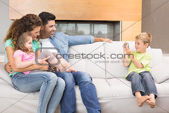 Little boy taking photo of family on the sofa