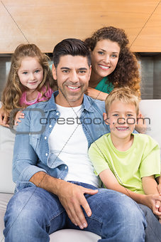 Happy family relaxing together smiling at camera