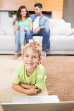 Happy little boy using laptop on the rug with parents sitting sofa