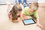 Smiling siblings lying on the rug using a tablet