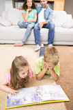 Happy siblings lying on the rug reading a storybook