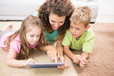 Happy siblings lying on the rug using tablet with their mother