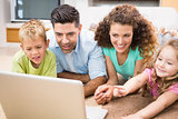 Cute siblings lying on the rug using laptop with their parents