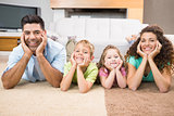 Happy siblings lying on the rug posing with their parents