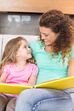 Happy mother sitting with her little daughter reading a storybook