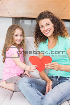 Smiling mother getting a heart card from her daughter