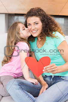 Smiling mother getting a heart card and a kiss from her daughter