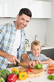 Happy father teaching his son how to chop vegetables
