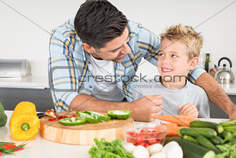 Smiling father preparing vegetables with his son