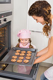 Mother taking cookies out of the oven with little girl watching