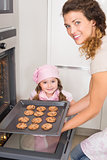 Mother taking cookies out of the oven with daughter