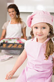 Cute girl wearing pink apron and chefs hat smiling at camera