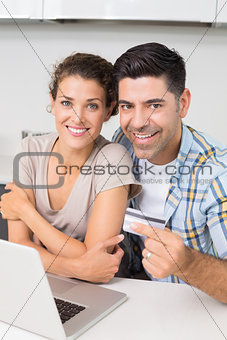 Attractive couple using laptop together to shop online