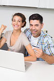 Excited couple using laptop together to shop online
