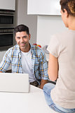 Cheerful man using laptop while partner sits on counter