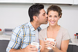 Cheerful woman drinking coffee getting a kiss from partner