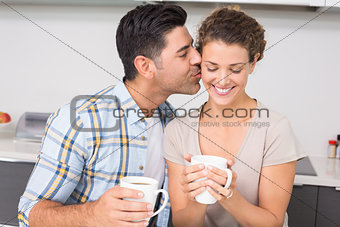Happy woman drinking coffee getting a kiss from partner