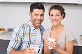 Happy couple having coffee smiling at camera