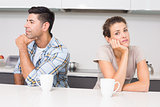 Troubled couple having coffee not talking