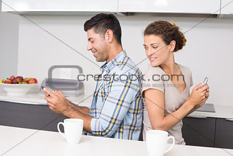 Attractive couple sitting back to back texting