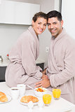 Smiling couple in bathrobes having breakfast together