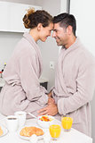 Romantic couple in bathrobes having breakfast together
