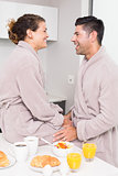 Happy couple in bathrobes having breakfast together
