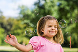 Girl looking at soap bubbles at park