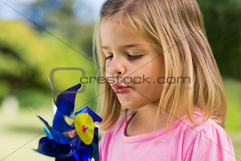 Cute girl blowing pinwheel at park