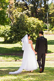 Rear view of newlywed couple walking in park