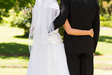 Mid section of a newlywed with arms around in park